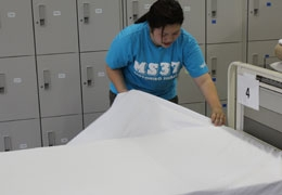 A student practicing making beds.